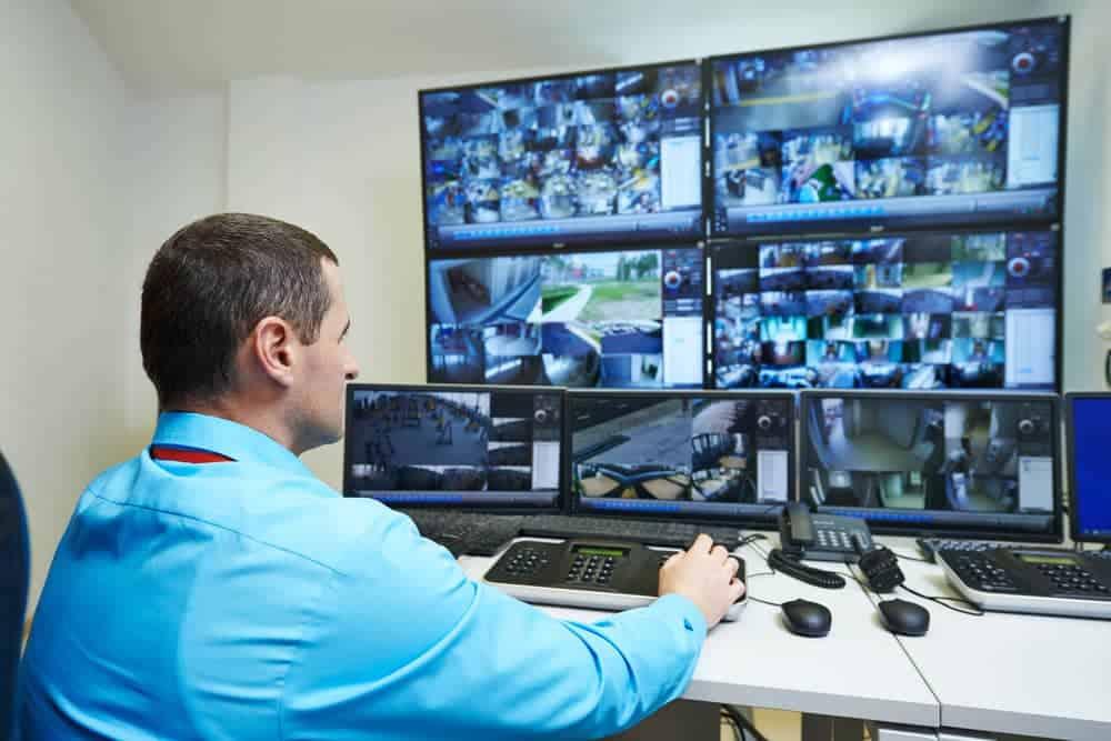 Security guard monitoring video screens